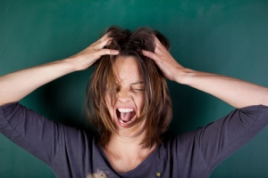 frustrated woman with hands in hair screaming against chalkboard